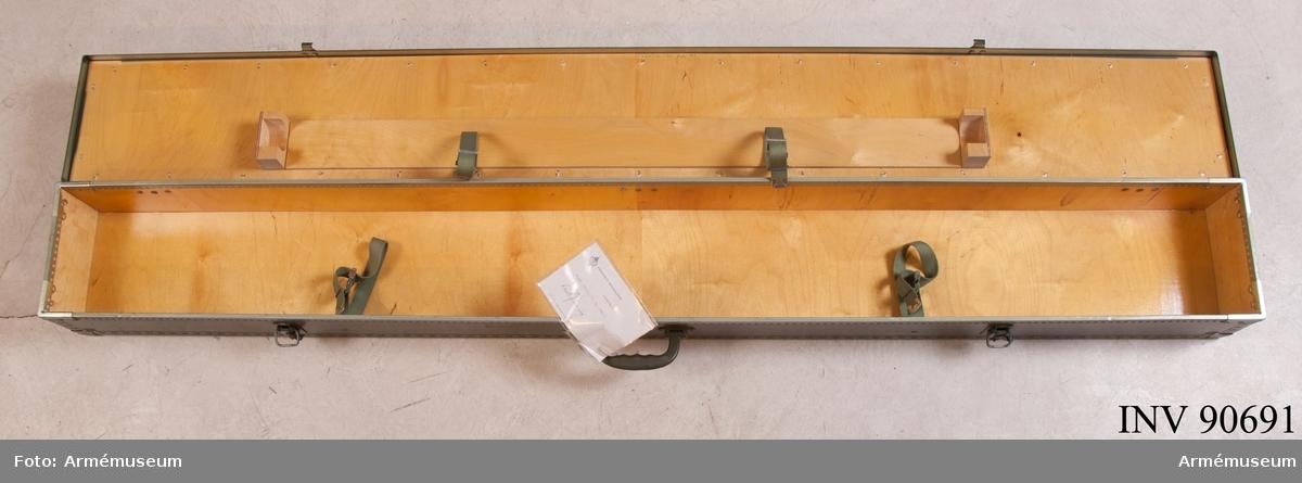 """Grön låda med handtag för transport av fana. I locket kan en del av stången fästas fast med hjälp av remmar. Vidhängande etikett: """"Försvarets materielverk, fastställs M 7680-990179-2, Tpr låda F, 1986-06-01, (oläslig underskrift), FMV 267.3. (FMV:Bekläd) 85-09. 1000 Ex""""."""