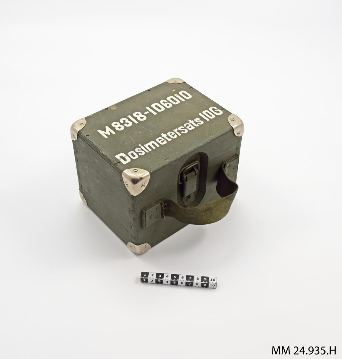 """Grön trälåda med lock och kanter skodda med blank metall. På framsidan spänne för att lås locket samt ett handtag i tyg. Text ovanpå locket:  """"M8318-106010 Dosimetersats 106""""  I lockets insida metallskylt fastskruvad med texten:  """"DOSIMETERSATS 106 Dosimeter 11            st 2 Dosimeter 21            st 2 Dosimeterladdare    st 1 801 eller 802""""  I lådan ställningar med borrade hål för dosimetrarna och plats jämte för dosimeterladdaren."""
