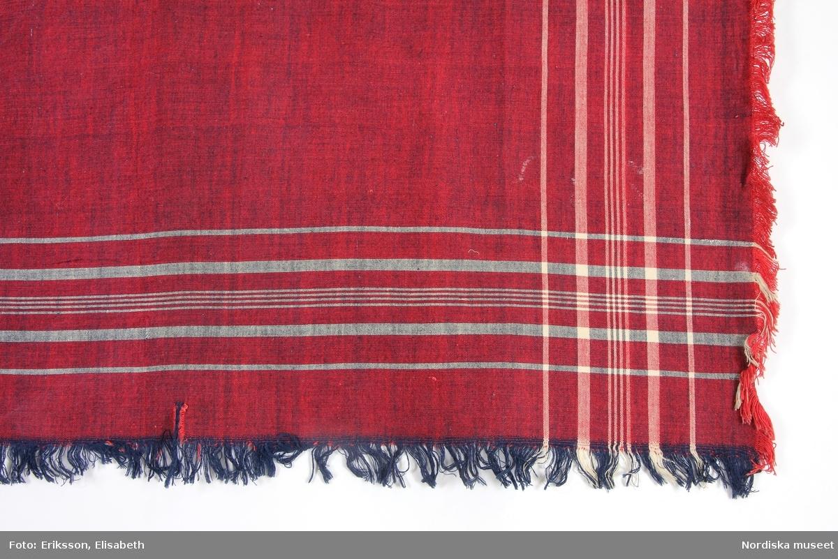 Kvadratiskt huvudkläde i bomullslärft,  röd varp och mörkblått inslag med vita smala kantränder, kort upprispad frans runtom. /Berit Eldvik 2012-01-24