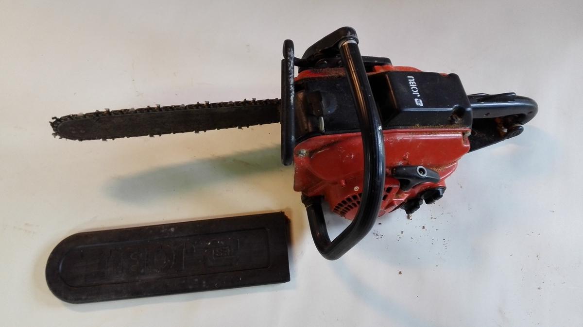 JOBU bensindriven motorsag med to-taksts motor. Motorkassen er oransjefarga og sagkjedet har beskyttelsesdeksel. Motorsaga har bruksanvisning med kjøpsbevis, katalogisert som nr. 32588
