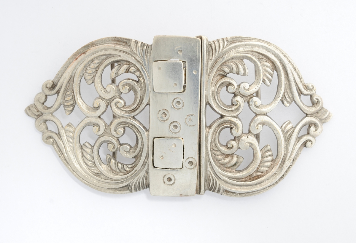 Beltespenne, A og B, støypt i sølv. Ope rosemønster som dekor. To firkanta haker til låsing på den eine delen (A), og hol som passar til på den andre (B).  På baksida to pålodda stenger.