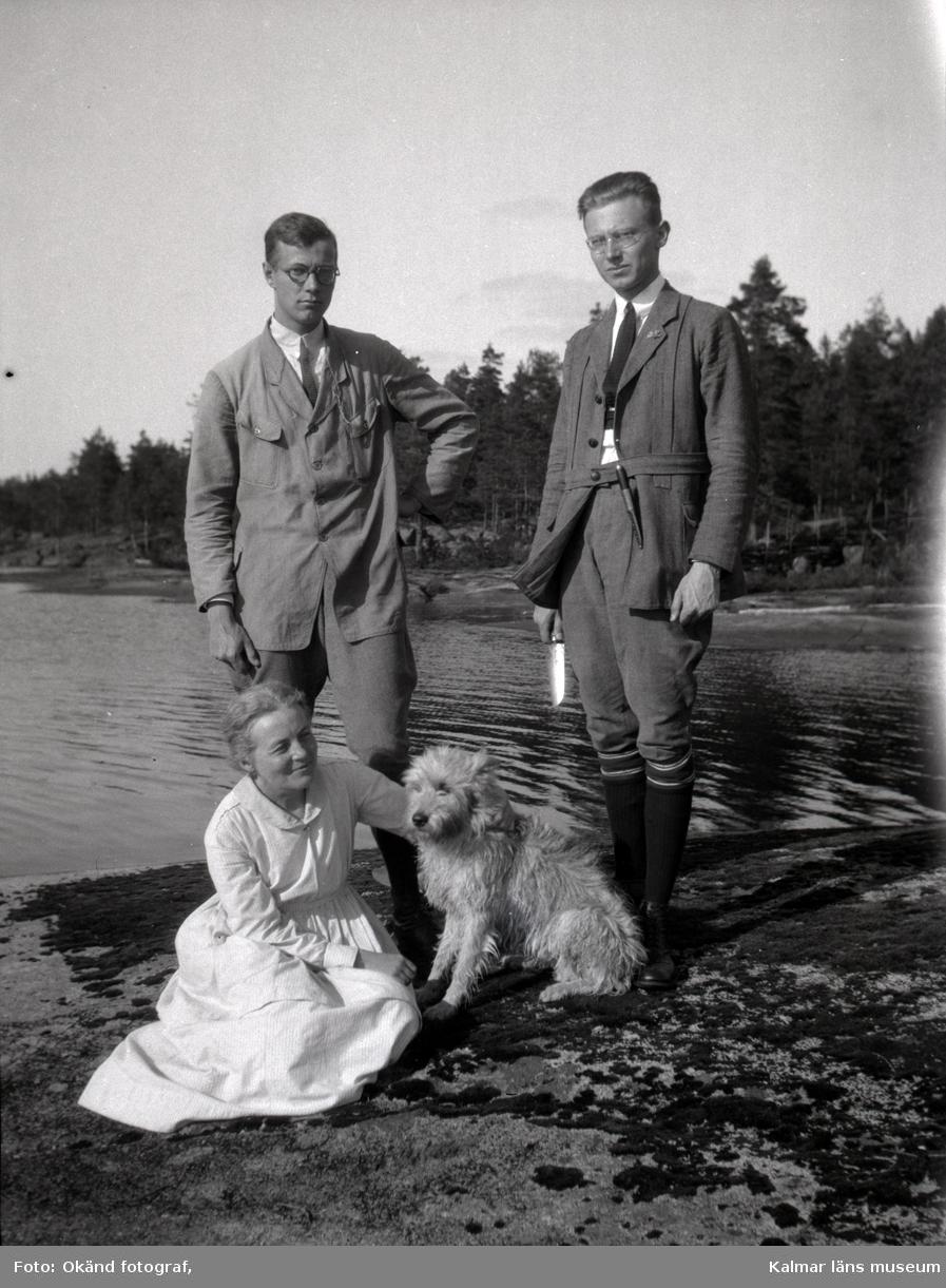 Gustaf och Kurt Seidler, Nina Hammarskjöld med hunden Jim liggandes på en klippa vid sjön Möckeln.