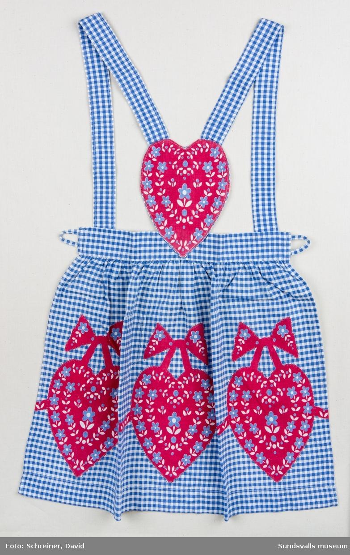 Ett smårutigt flickförkläde med hjärtmönster. Bröstlappen utgörs av ett hjärta och axelbanden knäpps korslagt i ryggen.