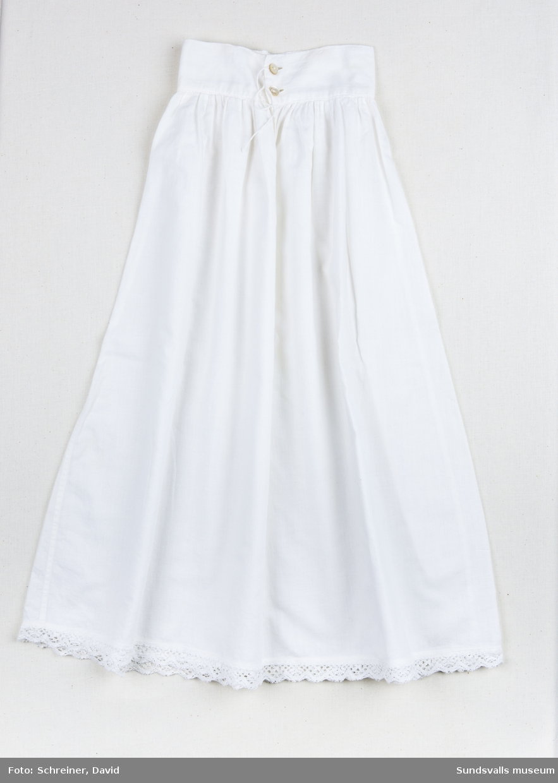 En vit bomullskjol med bred linning som knäpps baktill med två vita knappar. Kjolens nederkant har dekorerats med en brodyrspets.