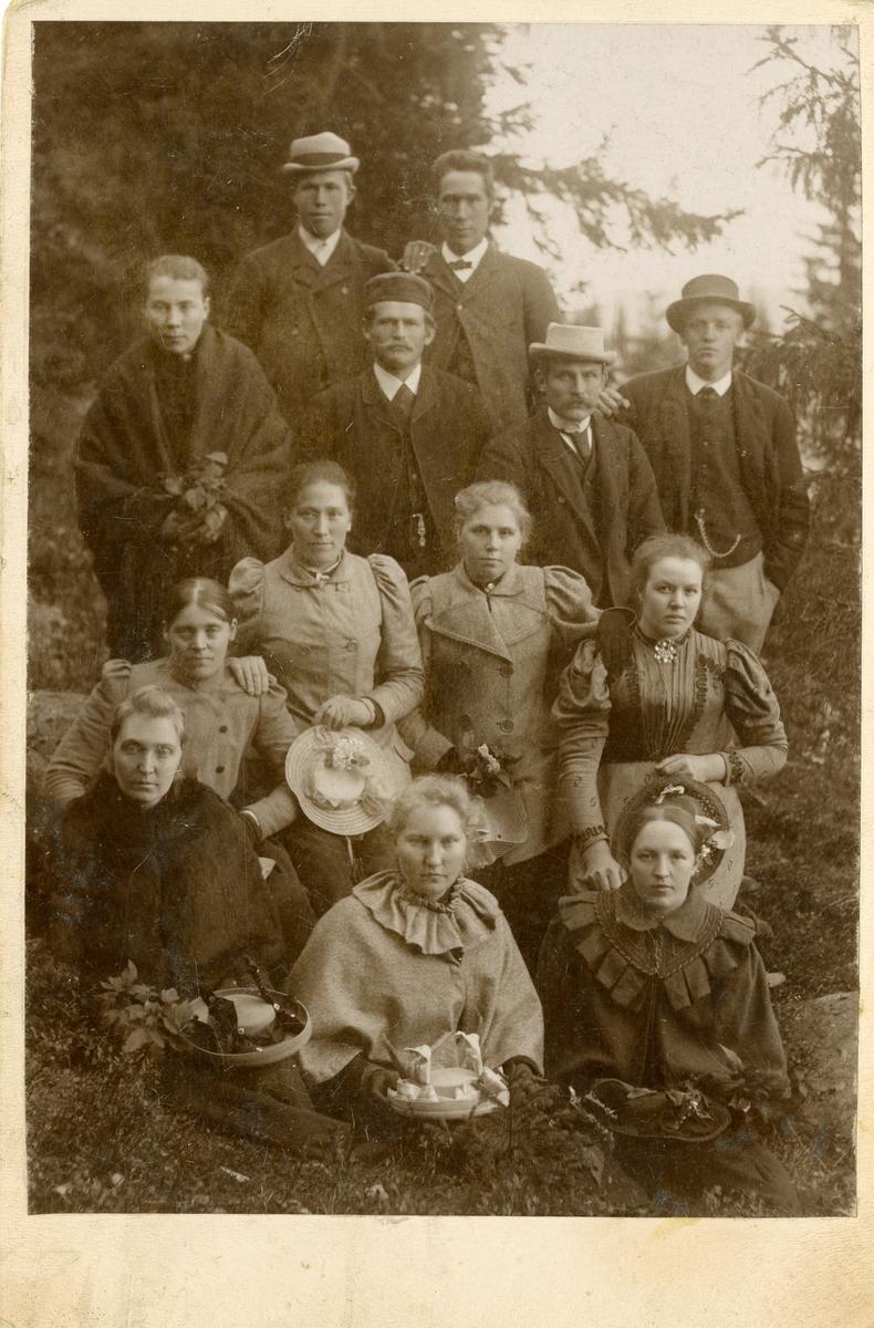 7 kvinner og 6 menn avbildet ute, foran noen grantrær.
