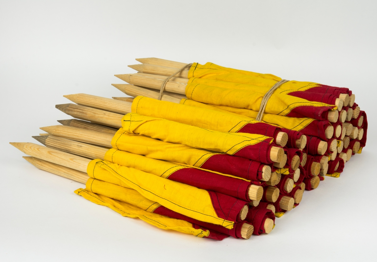 Markeringsflagga för flygfält och taxeringsbanor. Flagga sydd diagonalt av röd och gul bomullsduk fäst på en pinne. 50 stycken.