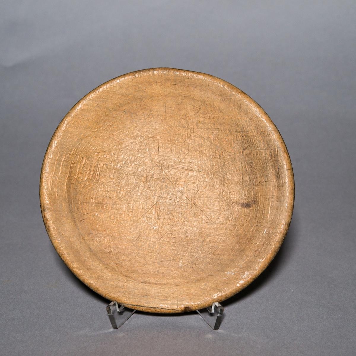 Tallrik av trä, trädisk, rund, svarvad. Rester av brunsvart färg.