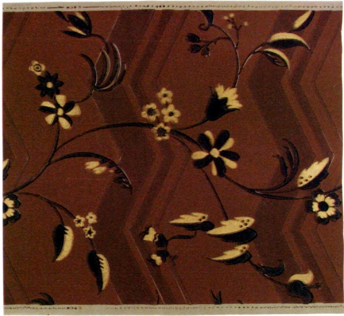 Stiliserade blommor och blad på en slingrande gren. Bakgrunden dekorerad med ett stort zickzackmönster. Tryck i svart och guld samt i två bruna nyanser.