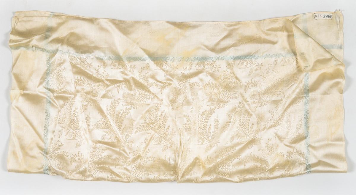 Tørkle i kremgul silkedamask med trykte turkise striper langs kantane. Falda med maskin.