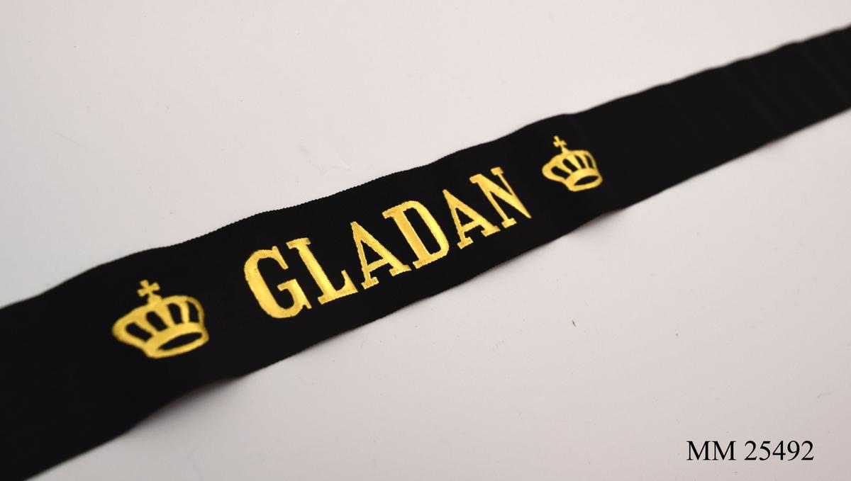 """Mössband av svart sidenrips. Guldfärgad text, """"Gladan"""", med två kronor på vardera sida."""