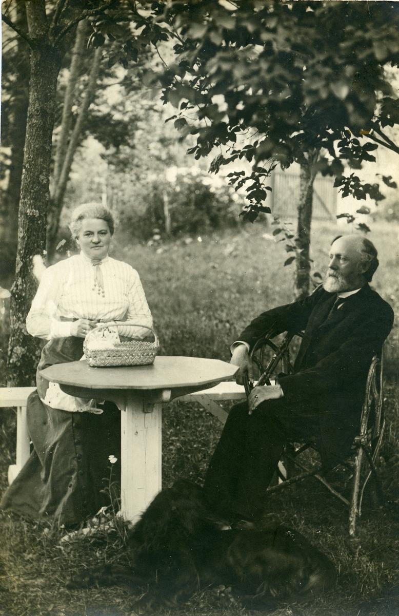 Prost Thomas Barth og kona Maren Marie sitter ved et bord i prestegårdshagen.