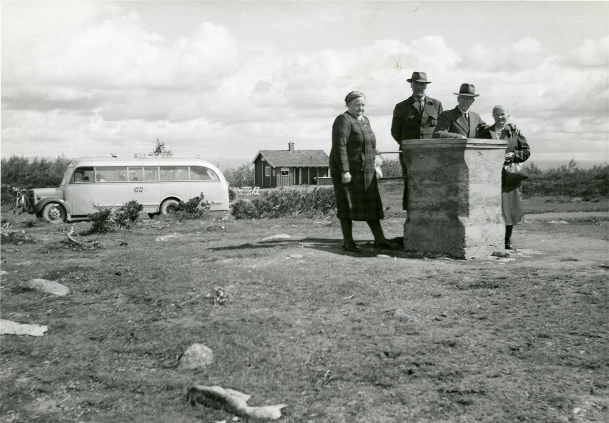 2 kvinner og 2 menn står rundt en merkestein på Gausdalsfjellet. Mannen til venstre er Gundbrand Brager, Hedalen, Sør-Aurdal.