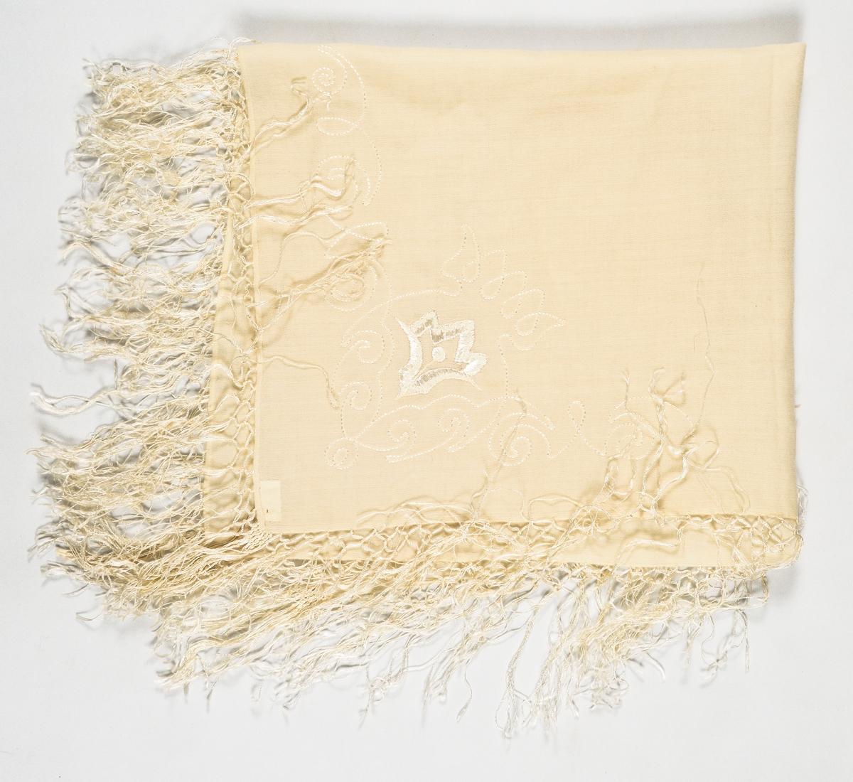 Tørkle i kremgul ullmusselin. Tamburert og brodert mønster med tynn lys silketråd i eine hjørnet. Påsette silkefrynser.