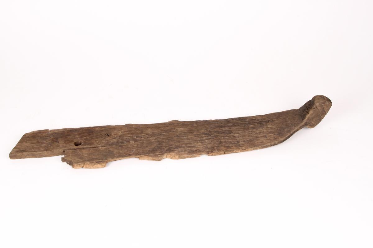 Øverste delen av en ski med et loddrett hull gjennom framskien, og en grovt formet og muligens uferdig tupp. Oversiden av skien er flat, det samme er undersiden. Skien har ingen rand under.