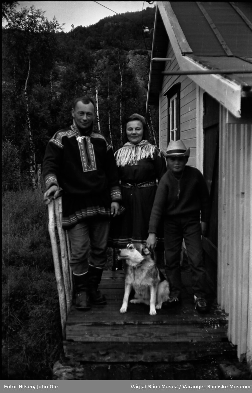 Et par kledd i kofte og en gutt med en hund står på en trapp. Ukjent sted, Juli 1967.
