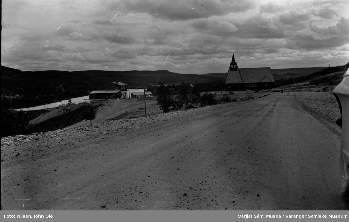 Masi kirke og et hus med et vann i bakgrunnen. Kyr beiter foran kirka. Máze / Masi, Juli 1967.