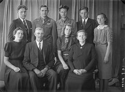 Gruppebilde. Familegruppe på ni. En eldre mann og kvinne, fi