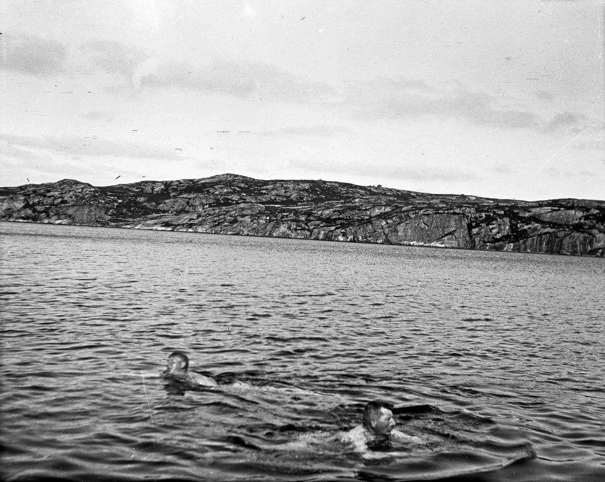 Kystlandskap. 2 menn bader i sjøen i forgrunnen. Landskap i bakgrunnen.