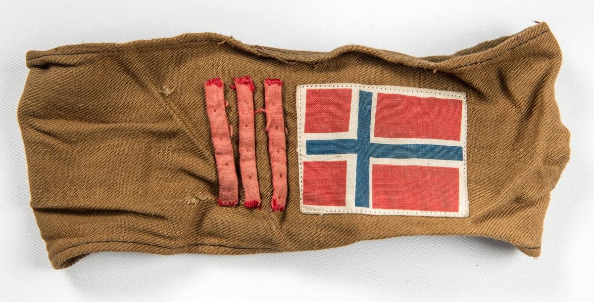 Armbind i brunt bomullstøy. Påsydd tre tynne raude striper og det norske flagget. Skreve med penn OSP. Var sett på ermet til VFF 09535 Uniformsjakke (med sikkerheitsnål).