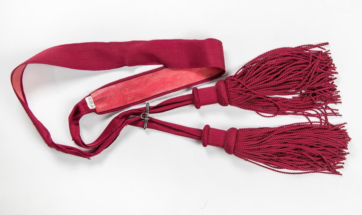 Band i raudt (burgunder) silke (?). med duskar i endane. Fóra med eit farga skinn.  Ei metallspenne.