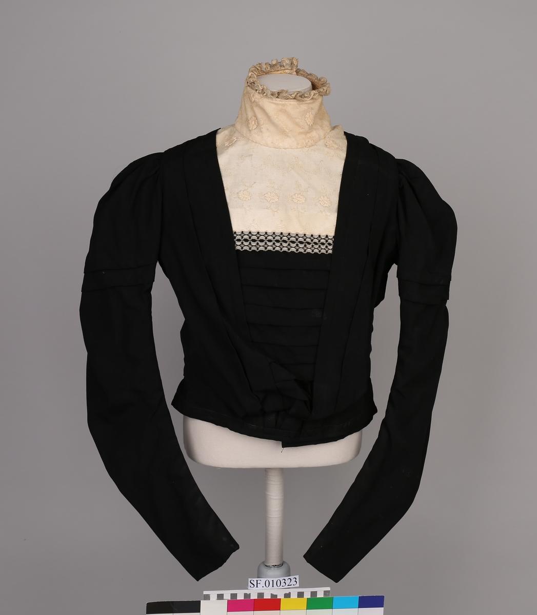 Overdel i svart stoff, blondekant. Lange ermer Kvitt halsparti, krage, mellom halsparti og framstykke er det satt på eit pyntebord i svart og kvitt.