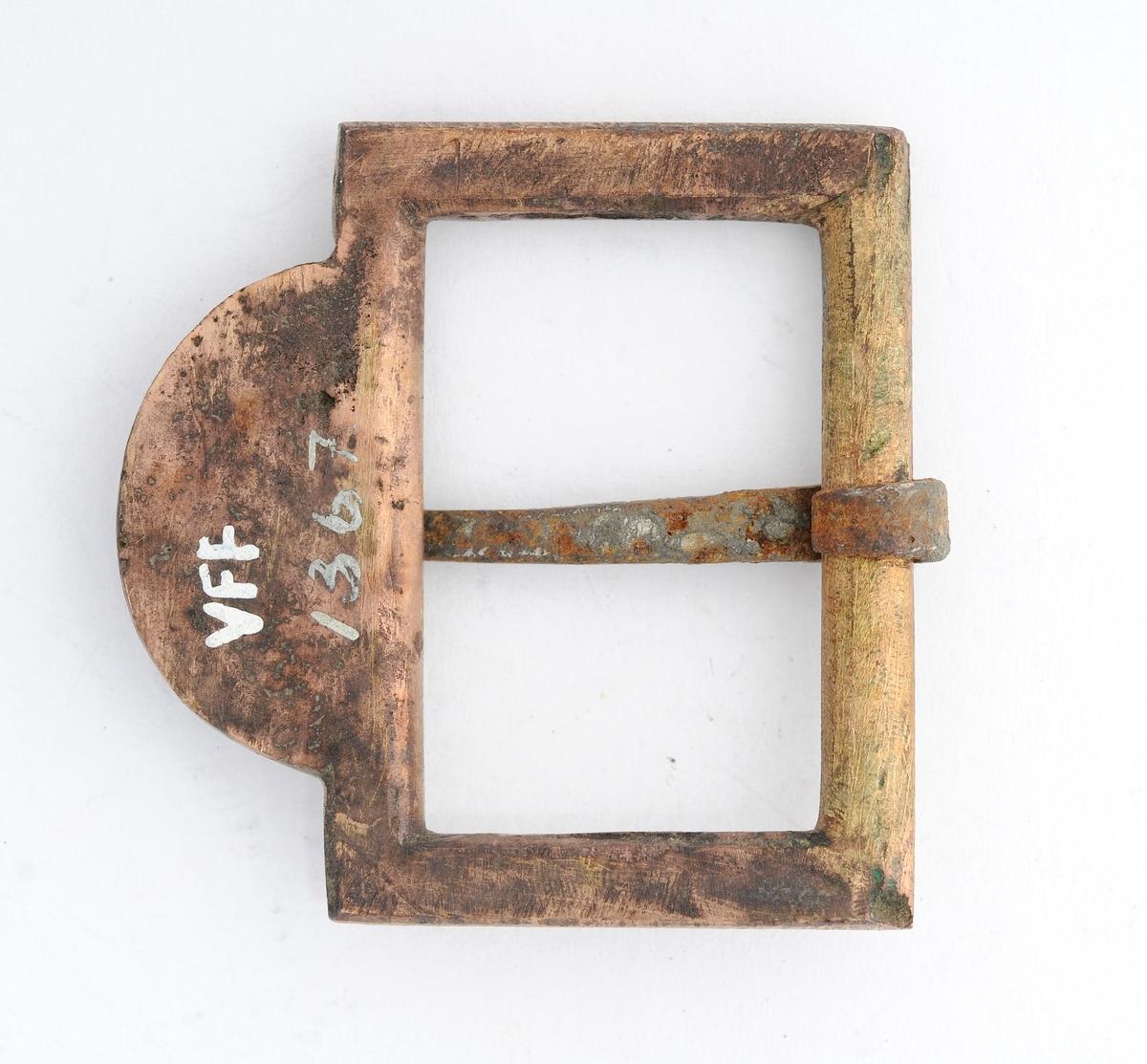"""Beltespenne i messing. Rektanguler flat form. Ingen dekor.  Stolpen er støypt i eitt med spenna med smidd tann rundt. Støypt flat """"halvmåne"""" på andre sida med årstallet 1806."""