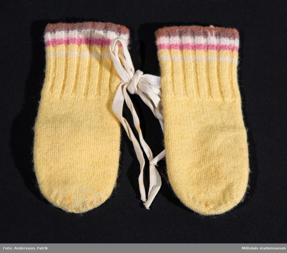 1 par barnvantar från 1967 som Karin ärvde från sin kusin. Karin använde dessa under sin spädbarnstid, 1978.  Vanten är benvit med ljusrosa, vit och brun rand vid handleden. Det finns ett vitt bomullsband fastsydd på varje vante som gör att man kan knyta ihop dom.