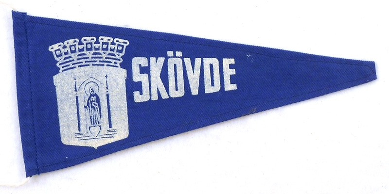"""Blå souvenirvimpelmed tryck i vitt. """"Skövde"""" samt stadsvapnet."""