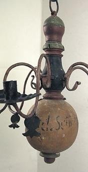 Ljuskrona målad i gult, svart rött och grönt med 6 smidda ljusarmar.  Vinköl står skrivet med blyerts på kronan.  Den har fram till 2002 fungerat som ljuskrona i Härjevadskyrkan i Fornbyn. Den togs in pga brandrisk och brandincident och ersattes med nytillverkad krona i samma stil. Tillsammans med 106208