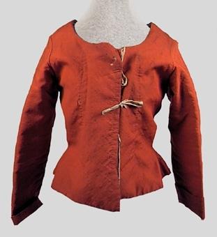 """Röd tröja av tuskaftsvävt ylletyg. Större delen av livet och ärmarna är fodrade med grovt linne. Livets nedre kant är fodrad med ett linne av finare kvalité. Modellen är sydd med öppning mitt fram, vid rundskuren halsringning, lång ärm med ärmuppslag samt skört mitt bak.   Fodret har en snörning mitt fram. Tre par knytband av bomull håller samman de båda framstyckena mitt fram. Livstyckets olika delar är sammanfogade med efterstygn, kaststygn samt förstygn.   Anm. enligt accessionskatalog:""""Lifstycke med armstycken af rödt tyg och fodrat med groft linnetyg samt framtill försedt med snören. Användt till en bruddräkt på 1780-talet"""""""