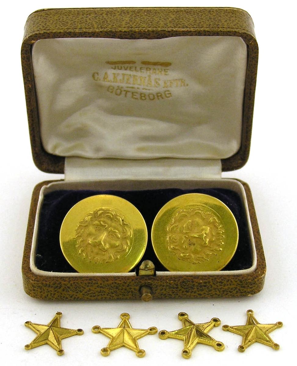 Två stycken knappar för Kungliga Västgöta regemente och fyra stjärnor (gradbeteckning). Förvaras i smyckeask märkt på insidan: Juvelerare C.A. Kjernäs eftr. Göteborg. Måtten avser asken. Tillverkaren avser endast den ena knappen.