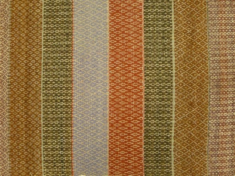 """Täcke vävt i bunden rosengång på tre skaft. Varp av oblekt lingarn. Inslag av entrådigt ull- och lingarn samt tvåtrådigt ullgarn. Täcket består av två våder vilka är sammmanfogade med en söm av kaststygn. Kortsidornas ytterkanter är fållade. Täcket är vävt i färgerna blåaktigt rött, brunt, rött, ljust blått samt oblekt lin. Anm. enligt accessionskatalog: """"Vävt av Maria Andersdotter år 1900. Maria Andersdotter = givarens farmor, född 1856 i Riddarhagen Bäreberg"""""""