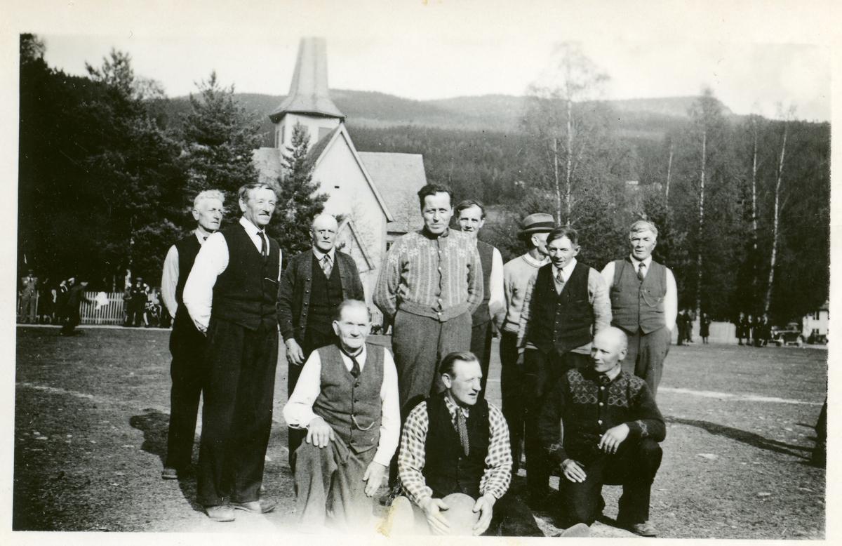 Gruppebilde av menn som står på Vangen ved Bagn kyrkje.
