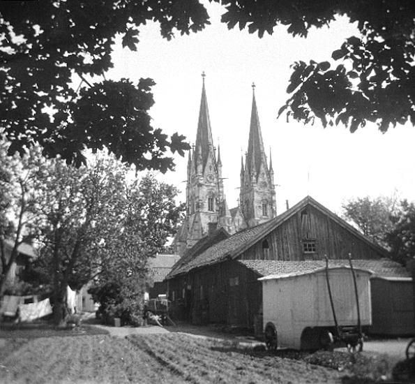 Bildtext: Skara Domkyrka. Kulturhistoriska undersökningen. Åkare Noréns gård i förgrunden.