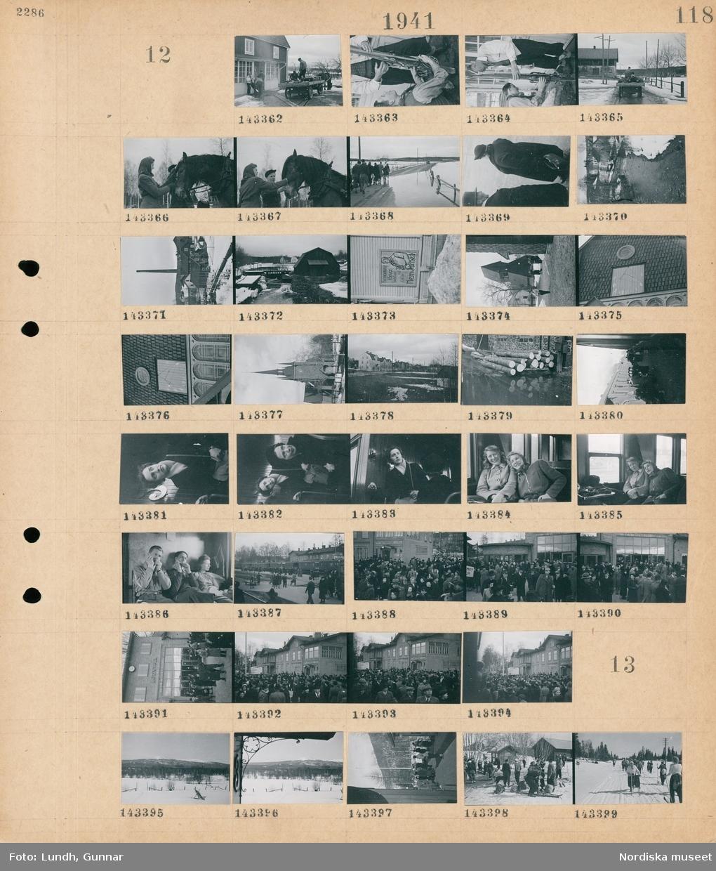 """Motiv: (ingen anteckning) ; En hästdragen vagn lastad med resväskor står framför ett hus med män som håller skidor står framför, en kvinna klappar en häst, en grupp kvinnor och män går på en översvämmad väg, landskapsvy med en å, vy över en fabrik, ett plakat """"Hemortens försvar behöver dig Gå in i Hemvärnet"""", exteriör av en kyrka med klocktorn, vy över bebyggelse, en stapel med timmerstockar, människor står vid ett tår, interiör av en järnvägsvagn med passagerare, två män spelar munspel på ett tåg, människor på perrongen på en järnvägsstation med skylt """"Ludvika"""", en folksamling framför en järnvägsstation.  Motiv: (ingen anteckning) ; En snötäckt landskapsvy med skog och fjäll, människor på perrongen vid ett tåg, kvinnor och män åker skidor i ett snötäckt landskap."""
