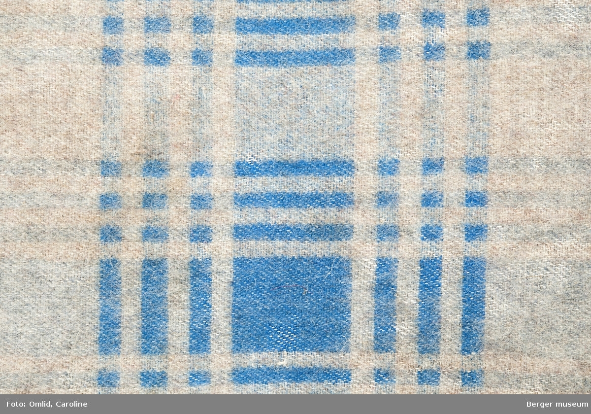 En prøve. Grå bunn, striper i lysblå og mellomblå i et rutemønster.