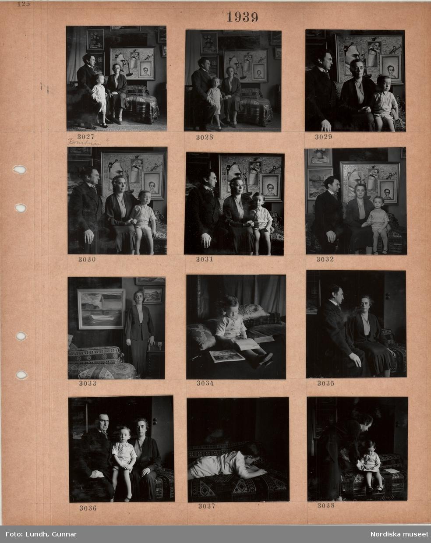 """Motiv: Man, """"konstnär?"""", kvinna och barn i ett rum med tavlor och schäslong, kvinna i dräkt står bredvid tavla med fiskebodar, liten pojke sitter och ritar i ett block, ligger på en schäslong och ritar i ett block, kvinna och ritande pojke."""