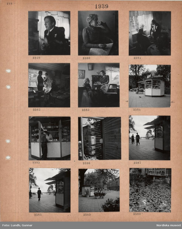 """Motiv: Sittande man, sittande kvinna med tidning i knät, två personer samtalar vid ett fönster, tidningsläsning, två kvinnor samtalar, kiosk vid en park, neonreklam """"WÅRBY vatten"""", ung man handlar vid kiosklucka, gata, trottoar, Nybroviken i bakgrunden, kiosk vid Nybroplan, damm med flytande lönnlöv."""