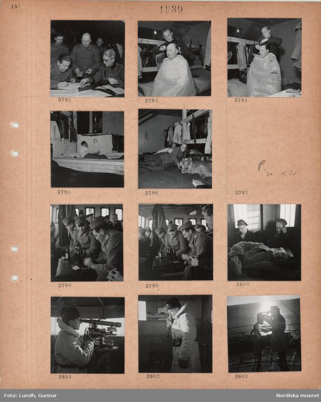 Motiv: Män i militärkläder, män vid skrivbord, pengar, logement med hoprullade madrasser, klädkrokar med kläder och gevär, en man klipper håret på en annan man med skynke över sig, en man ligger på en madrass och ritar en bild av en kvinna på väggen, man som kelar med en hund, män spelar kort(?) på en resväska, ölflaskor, pengar, sovande män på bänkar, en man i päls tittar i ett mätinstrument, talar i telefon.
