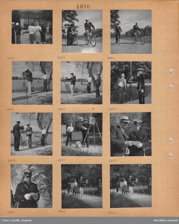 Motiv: Utomhusscen i park med orkester, publik, två män med cyklar på grusväg, två män med uppställda stafflier står på en väg vid vatten, en man i kostym och ljus hatt tittar på när två män målar, en man i kostym hälsar på en uniformerad polis som gör honnör, uniformerad polis kontrollerar de målande männens handlingar.
