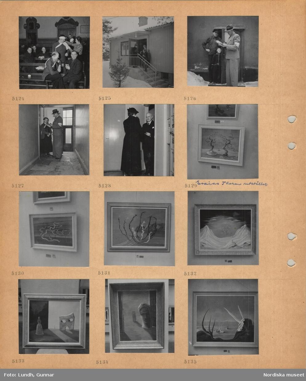 Motiv: Övning i att lägga förband, entrétrappa till småhus, snö, en man med portfölj och ytterkläder, kvinna i dörren, två barn, man i kostym och ljus armbindel antecknar i papper vid husentré med man och liten flicka, kvinna vid lägenhetsdörr, kvinna i ytterkläder och man i kostym vid lägenhetsdörr, Esaias Thorén utställer, inramade målningar på vägg i utställningssal.