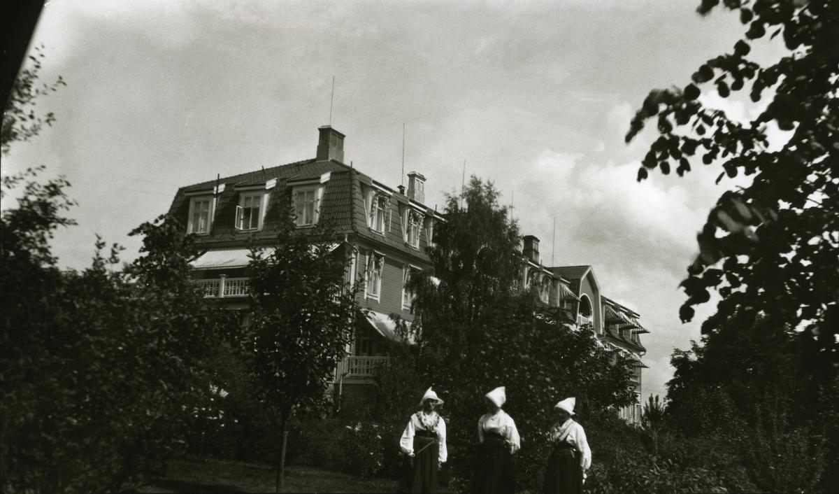 Tre svenske kvinner (i bunad) foran enormt hus; Siljansborg (Sverige).
