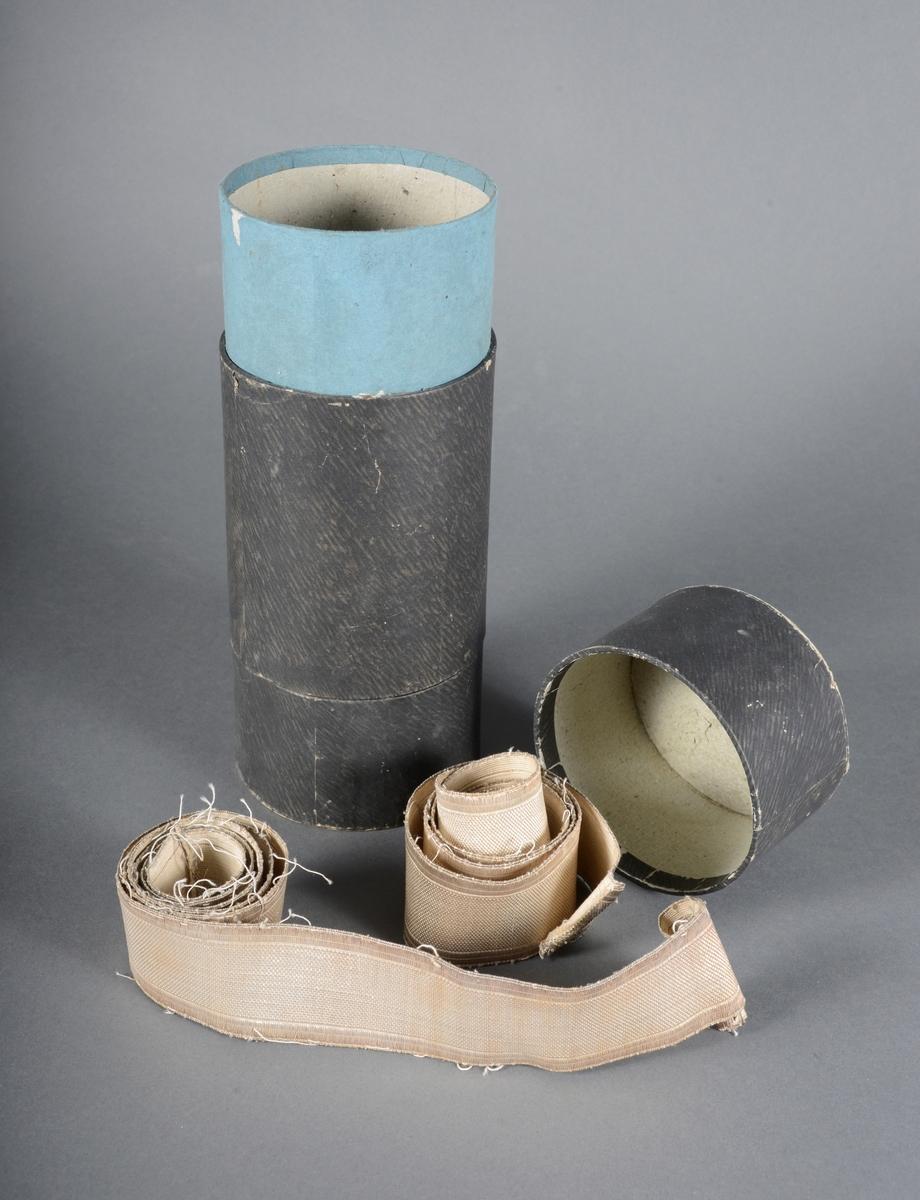 Sylindrisk eske til kokarde fjerbusk for borgergardeuniform. Eska inneholder nå to remmer (bukseremmer og bukgjord).