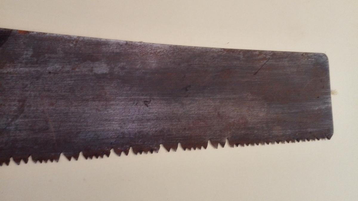 Forholdsvis stor stikksag med fint utforma trehandtak. Sagtennene har ulik lengde, i eit mønster som skal gjera saga eigna til kløyving (saging på langs av treet).