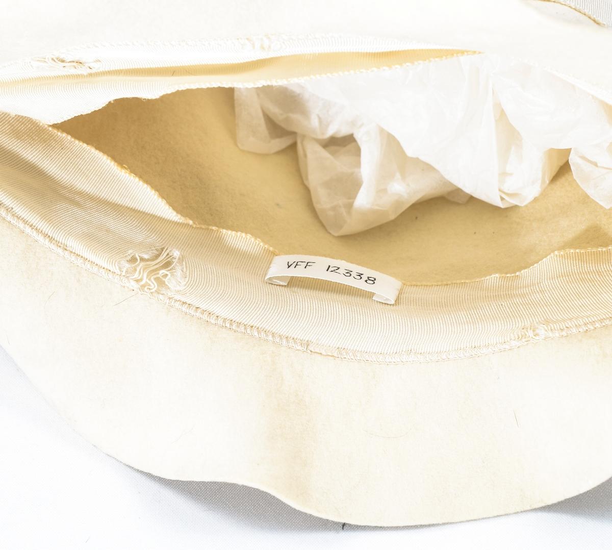 Lue, hatt i beige filt. Ripsband rundt med sløyfe bak. Påsydd ripsband på innsida også.