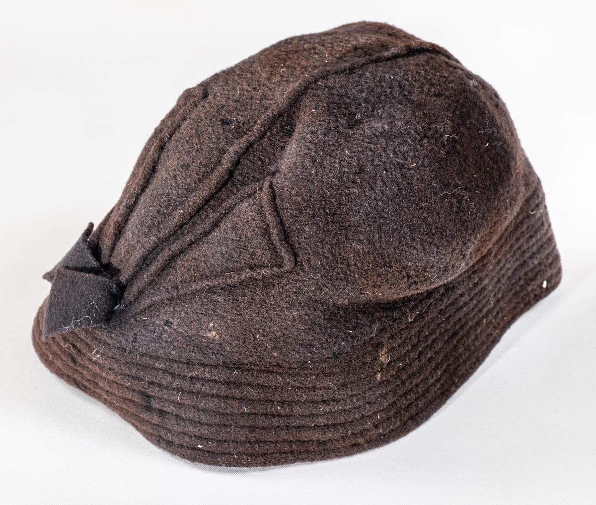 Lue, hatt i brun filt. Vattert brem rundt. Sydde biser til pynt. Sløyfe midt bak.