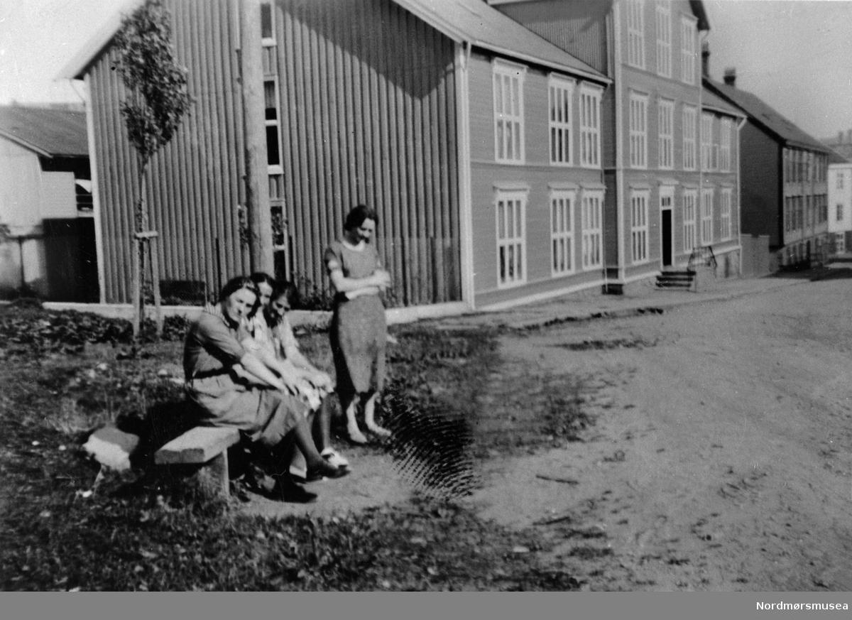 4 jenter på en benk. Er Marstrandsgata nylig fullført? Kristiansund 1920-30? Nordmøre museums fotosamling