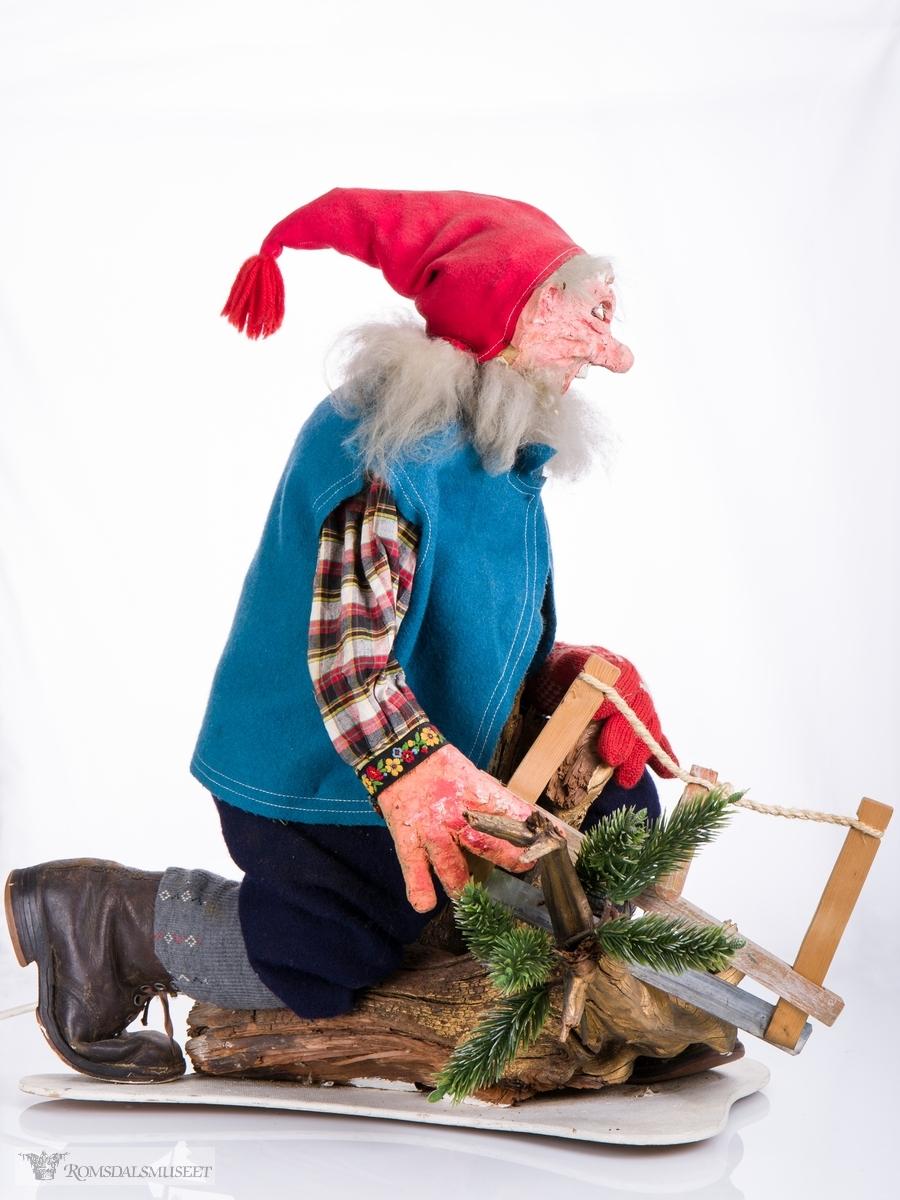 Mekanisk juledekorasjon bestående av en nisse som sitter på en fururot med en grindsag. Nissen er kledd i skjorte, vamdelsvest, knebukser, knestrømper og beksømsko. Tilkoblet ledning med av og på knapp.