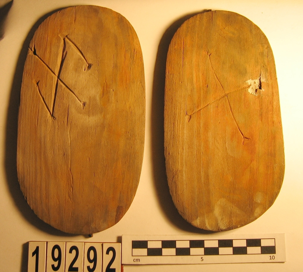 En svepask, i delar. Delarna utgörs av ett lock, en botten samt fragment av svepet. Locket och botten är båda försedda med varsitt bomärke.