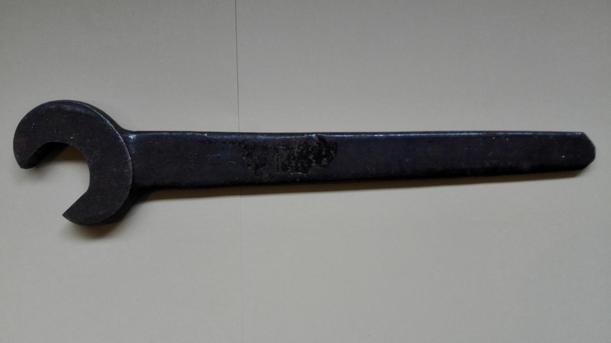 Fastnøkkelen er produsert i eitt stykke stål med ein kjeft i eine enden. Handtaket smalnar av frå kjeften og mot andre enden.